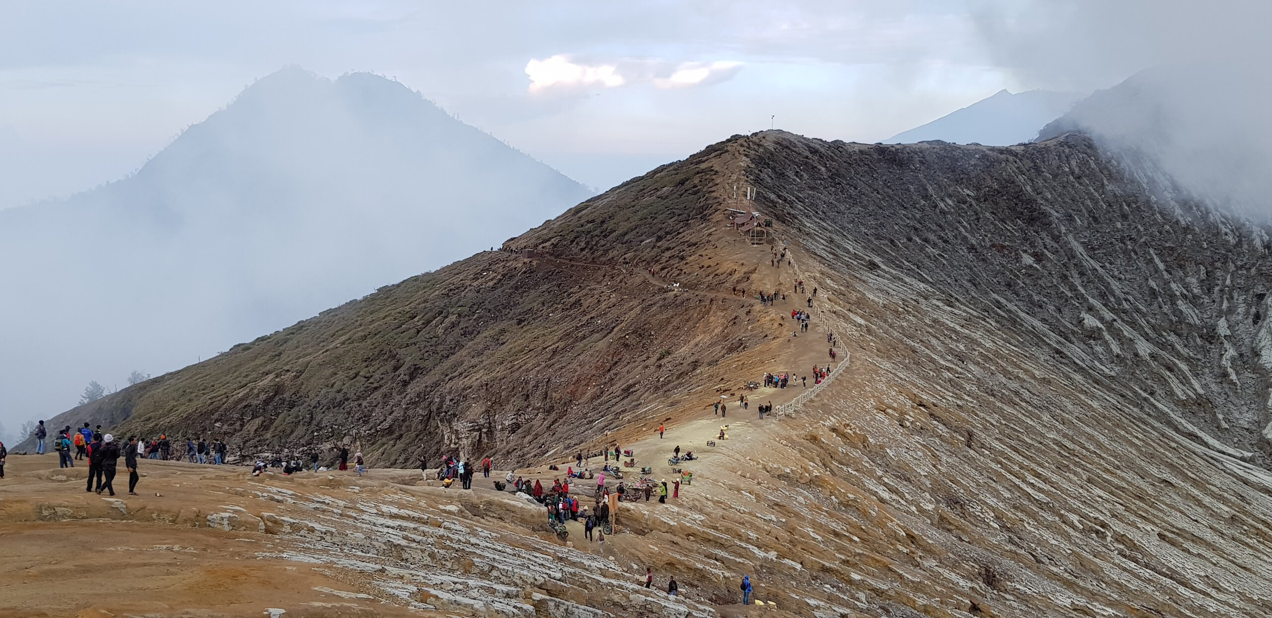Tourists idling at the crater rim of Ijen volcano, making last selfies before going back to the base camp.