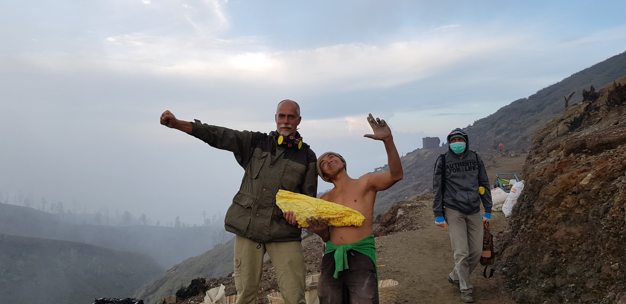 A sulphur miner with a chunk of sulphur at Ijen volcano, posing with the author for a silly selfie.
