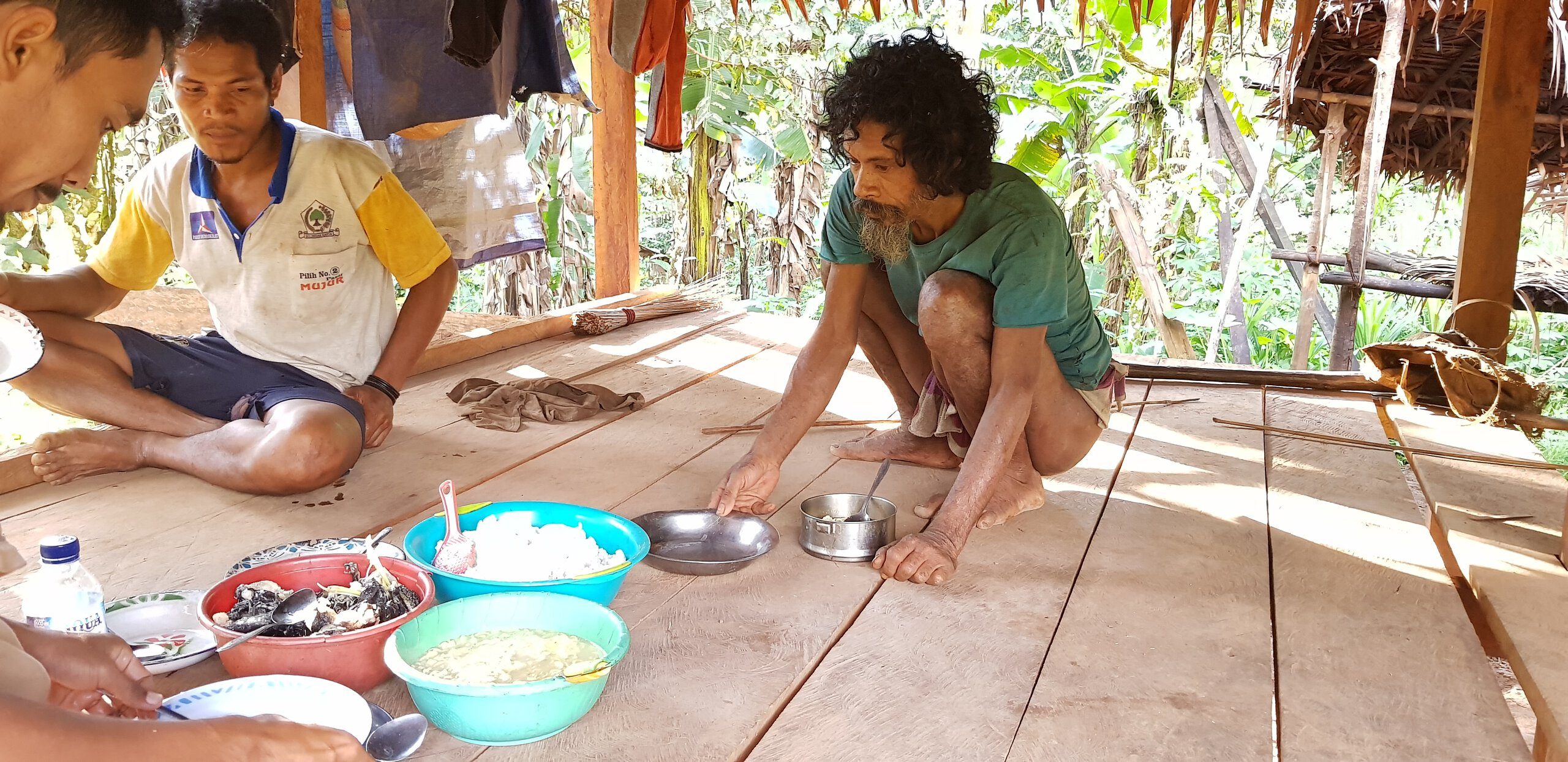 Pak Pojiji, the oldest Togutil in the settlement (right) is having a lunch with his guests. His house was built for him by Antam, a company mining nickel in Halmahera.